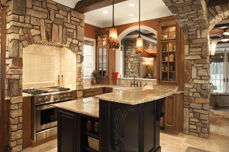 Upscale kitchen interior with stone accents and wood beam ceiling. Horizontal shot. Stock Photo