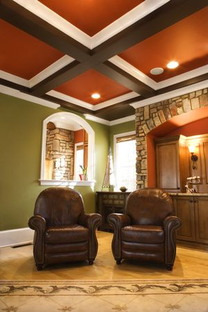 architectural lighting design: Two brown leather chairs in an upscale living room with wooden box beam ceiling and stone arch accents. Vertical shot. Stock Photo