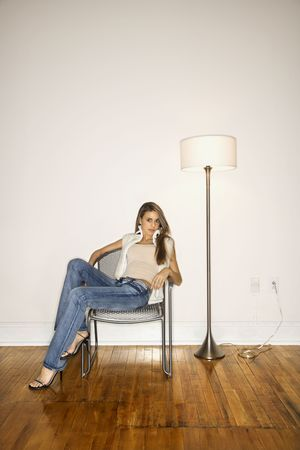 Attractive young woman slouching in a silver chair next to a floor lamp. She is looking towards the camera. Vertical shot. photo