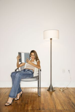 sitting on floor: Attractive young woman sitting back in a silver chair and reading a book next to a floor lamp. Vertical shot.