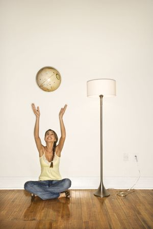 Attractive young woman smiling and sitting on the floor next to a floor lamp. She is tossing a globe into the air. Vertical shot. photo