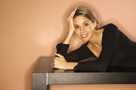 Attractive young woman lying on a table smiling. Horizontal shot photo