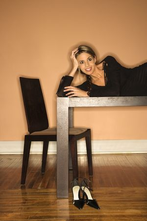 Attractive young woman lying on a table and smiling. She has placed her shoes on the floor. Vertical shot photo