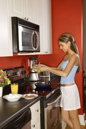 Attractive young woman smiling in her kitchen while cooking breakfast. She is dressed in sleepwear. Vertical shot. photo