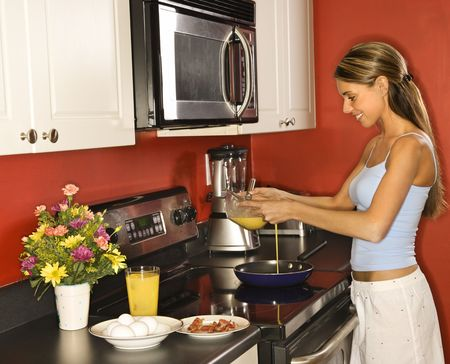 Attractive young woman smiling in her kitchen while cooking breakfast. She is dressed in sleepwear. Horizontal shot. photo