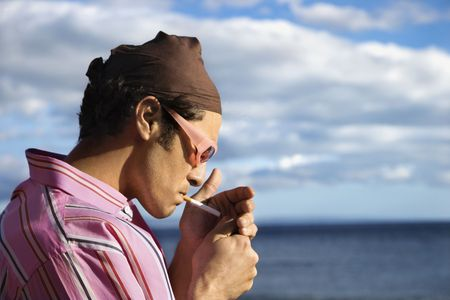 Close-up of a young man standing by the ocean and lighting a cigarette. Horizontal shot. photo