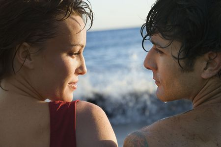 Cropped close-up of young man and woman, wet from swimming, looking at each other, with the ocean in the background. Horizontal shot. photo