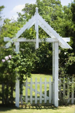 A gated arbor entrance into a spacious green lawn. Vertical shot. photo