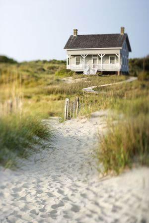cottages: A sandy trail surrounded by brush leading up to a cottage on the beach. Vertical shot. Stock Photo