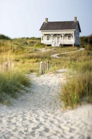 시골집: A sandy trail surrounded by brush leading up to a cottage on the beach. Vertical shot. 스톡 사진