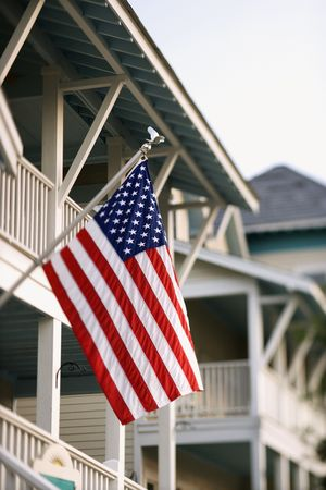 flagpoles: An American flag hanging from a flagpole on the front of a home. Vertical shot.