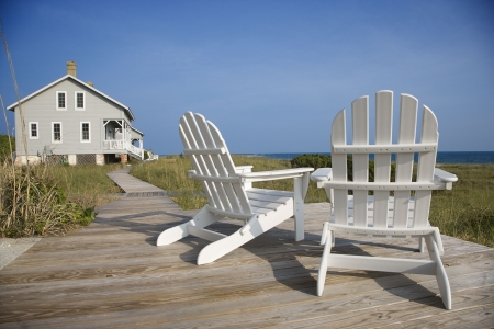 beach chairs: Two Adirondack style chairs sitting on a wooden deck, facing the shore. There is a large home in the background. Horizontal shot. Stock Photo