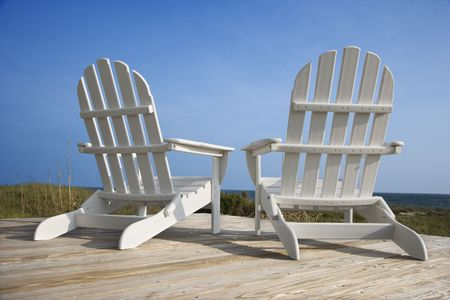 chairs: Rear view of two white Adirondack style chairs sitting on a wooden deck, facing the beach. Vertical shot.