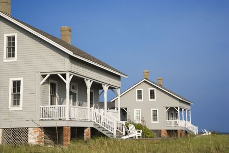 cropped: Cropped, low angle view of two identical looking beachfront homes against a backdrop of a clear, blue sky. Horizontal shot. Stock Photo