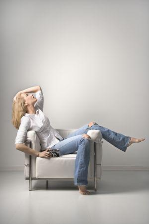 mujeres sentadas: Perfil de una mujer joven sentada en una silla en la celebraci�n de una c�mara. Un disparo vertical. Aislados en blanco.