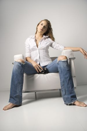 women jeans: Low angle tilted view of a young woman seated in a white armchair and holding a camera. Vertical shot.