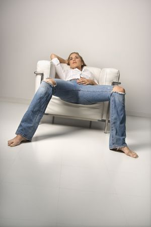 Low angle tilted view of a young woman relaxing in an armchair. Vertical shot. Stock Photo - 6420576