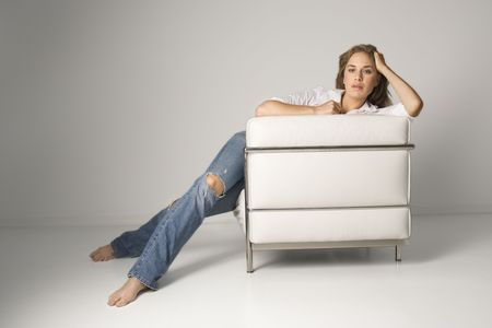 A young woman relaxing in a white armchair and looking at the camera. Horizontal shot. photo