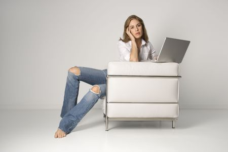torn: A young woman sitting in a white armchair with a laptop computer, looking at the camera. Horizontal shot.