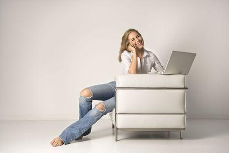 Een lachende jonge vrouw zitten in een witte fauteuil met een lap top computer, praten op een mobiele telefoon. Horizont aal schot.