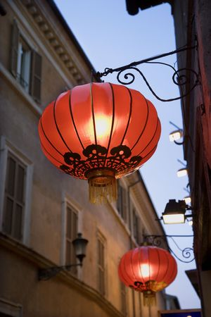 Low angle view of illuminated red paper lanterns hanging outside on a building facade. Vertical shot. photo