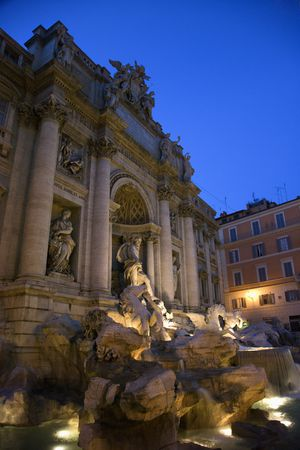 statuary: Trevi Fountain at night with lights under the water lighting the statuary. Vertical shot.