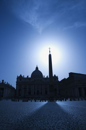 The east facade of St Peters Basilica with the obelisk in the foreground. The sun is directly behind the obelisk. Vertical shot.