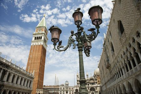 Bell tower and street lamp with facade of St Marks Basilica. Horizontal shot.