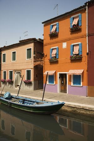 awnings: Buildings and boat on a canal in Venice, Italy, under blue sky. Vertical shot.