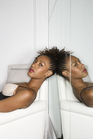 woman mirror: Attractive young woman reclining in a white chair with a mirror behind her head. Vertical shot.