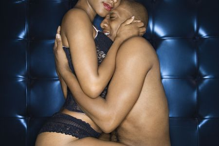 Attractive young couple embracing. The man is shirtless and the woman is wearing sexy lingerie. Horizontal shot. photo