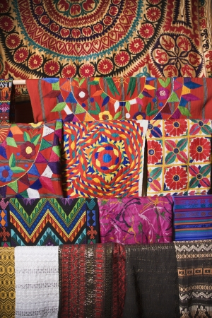Colorful Mexican patterned fabric hanging on a rack. Vertical shot. photo