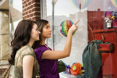 Young women pointing to items in an interior design store window. Horizontal shot. photo