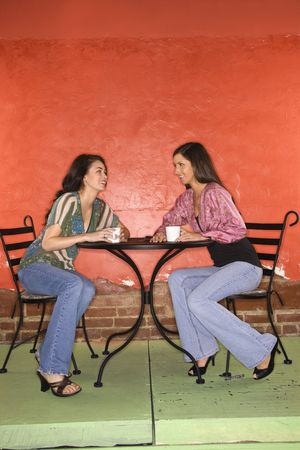 coffee table: Two young adult women sitting in a cafe, having coffee and talking. Vertical shot. Stock Photo