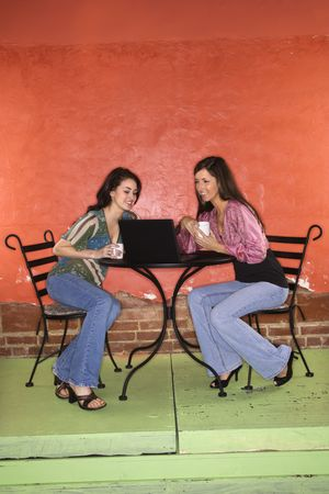 Two young adult women sitting in a cafe, having coffee and using a laptop. Vertical shot. photo