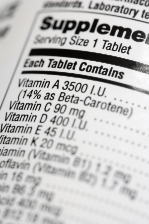 contained: Closeup of a dietary supplement label listing the vitamins contained within each tablet. Vertical shot. Stock Photo