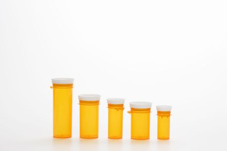 Yellow medicine bottles in diminishing sizes lined up in a row. Horizontal shot. Isolated on white. Stock Photo