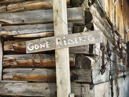 days gone by: GONE RIDING sign against an old weathered, wooden stable. Horizontal shot. Stock Photo