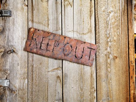 Rusty sign reading KEEP OUT. It is hanging on an old weathered wooden door. Horizontal shot. photo