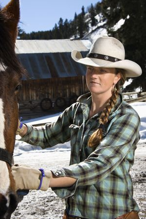 Attractive young woman wearing a cowboy hat and petting a horse. Vertical shot. photo