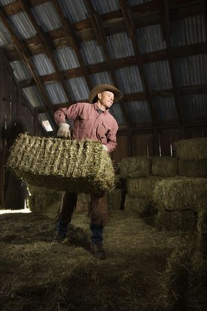 bale: Man wearing a cowboy hat and carrying bales of hay in the barn. Vertical shot.