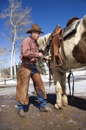 Man standing next to a horse while cinching up a saddle. Vertical shot. Stock Photo - 6429175