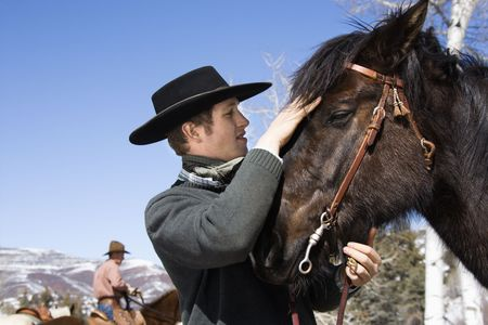 Attractive young man wearing a cowboy hat. He is petting a horse with another rider in the background. Horizontal shot. photo