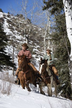Man and young woman riding horses up a snowy hill on a country landscape Vertical shot. Stock Photo - 6429014