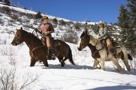 Man and young woman riding horses in deep snow across a country landscape. Horizontal shot.