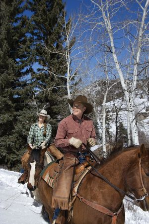 winter woman: Man and young woman riding horses in the snow. Vertical shot. Stock Photo