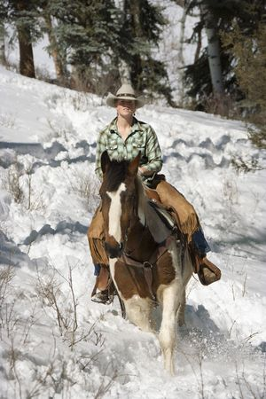 Attractive young woman riding a horse in the snow. Vertical shot. photo