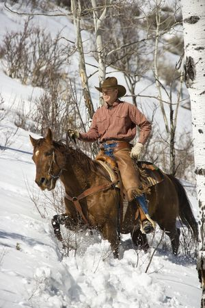 Cowboy in chaps riding a horse in the snow. Vertical shot. Stock Photo