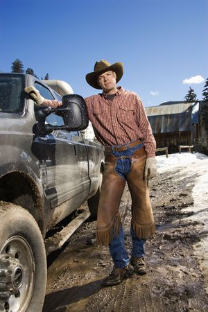 leaning on the truck: Man wearing a cowboy hat and leaning against a pickup truck. Vertical shot