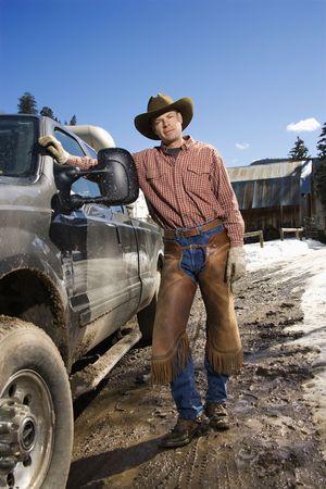 cappello cowboy: Uomo indossa un cappello da cowboy e pendente contro un camioncino. Verticale di tiro Archivio Fotografico